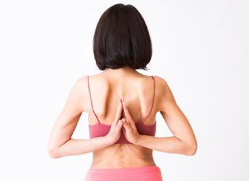背中で合掌しています。肩甲骨周りの筋肉の柔軟性が必要です。