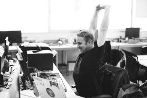 仕事の合間に背伸びをする男性